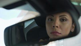 Damezitting in auto, haar gedachtengang in achteruitkijkspiegel, verdachte schaduwrijke handelaar stock footage