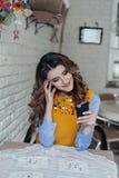 Damezitting bij de lijst in koffie die telefoon met behulp van Royalty-vrije Stock Afbeelding