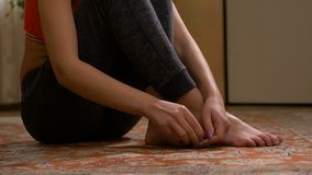 Damezitting op vloer die haar tenen masseren stock video