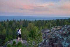 Damfotvandrare med ryggsäckflyttning till överkanten av berget på solnedgången royaltyfria foton