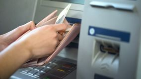 Damhänder som sätter ryska rubel i plånboken, kassa som återtas från ATM, turism royaltyfri foto