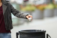 Damhand som kastar avskräde till ett avfallfack Arkivfoto