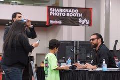 Damien Sandow habla con la fan del niño mientras que la mamá toma la foto en el teléfono móvil Foto de archivo libre de regalías