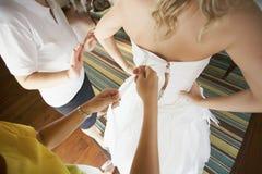 Damigella d'onore che contribuisce a mettere il vestito bianco di lusso elegante dalle spose Fotografie Stock Libere da Diritti