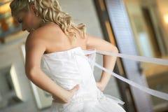 Damigella d'onore che contribuisce a mettere il vestito bianco di lusso elegante dalle spose Fotografia Stock