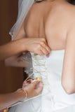 Damigella d'onore che lega arco sul vestito da sposa Fotografie Stock