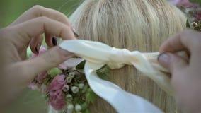 Damigella d'onore che lega fascia per la bella sposa bionda sul suo giorno delle nozze Corona nuziale del fiore sulla testa video d archivio