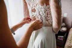 Damigella d'onore che lega i nastri sul vestito bianco da nozze Immagini Stock Libere da Diritti