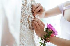 Damigella d'onore che prepara sposa per il giorno delle nozze Immagine Stock