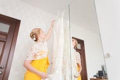 Damigella d'onore con i bottoni del vestito della sposa Immagine Stock