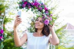 Damigella d'onore fotografata davanti all'arco per le nozze cer Immagine Stock Libera da Diritti