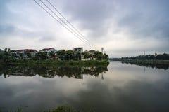 Damm i centrumstaden på bakgrund Två-våning herrgårdar på sjön oklarheter reflekterat vatten arkivfoto