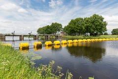 Damm i den holländska floden Vecht med att sväva barrikaden royaltyfri fotografi