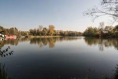 Damm med buidling av Lodenice på banken, färgrika träd på Park Bozeny Nemcove i den Karvina staden i Tjeckien under höst arkivbilder
