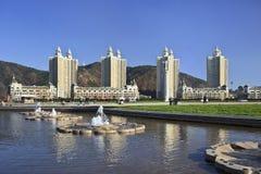 Damm och hyreshusar, Xinghai kvadrerar, Dalian, Kina och ett damm Royaltyfri Foto