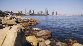 Damm von Baku, Aserbaidschan Das Kaspische Meer, die Steine und die Wolkenkratzer stock footage