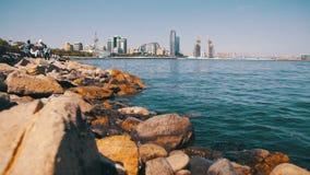 Damm von Baku, Aserbaidschan Das Kaspische Meer, die Steine und die Wolkenkratzer stock video footage