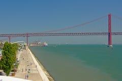 Damm von Fluss der Tajo und Brücke vom 25. April herein des Hafens von Lissabon, stockbild