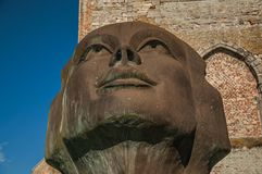 Close up of a big stone statue of two cast heads in garden of medieval church ruins at Damme stock image