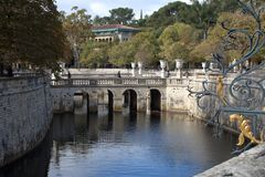 Dammet som framme omges av broar av ingången till Jardinsen de la Fontaine arkivfoto