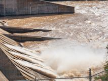 Dammluckor öppnar på en fördämning för elströmutveckling royaltyfri foto