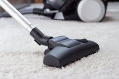 Dammsuga en vit matta för tjock hög Arkivfoto