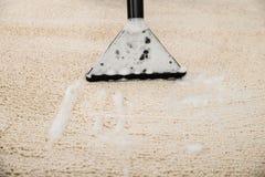Dammsugare över matta Arkivfoto