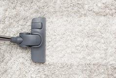 Dammsugare gör ren den vita lurviga mattan royaltyfri bild