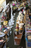 The Damnoen Saduak Floating Market about 60 miles from Bangkok Thailand. Selling food and straw hats from boats in the marketplace at the Damnoen Saduak Floating Royalty Free Stock Images
