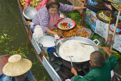 People sell food from boats at the floating market in Damnoen Saduak, Thailand. Stock Photos