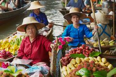 Women sell fruits from boats at the floating market in Damnoen Saduak, Thailand. Royalty Free Stock Image