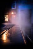 Dampf, der in der Nacht durch Straße steigt Stockbilder