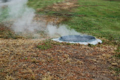 Dampf kommt aus den Abwasserkanal heraus Stockfotos