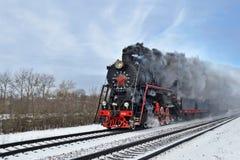Dampfzug, der entlang den Bahnen luftstößt Lizenzfreie Stockfotografie