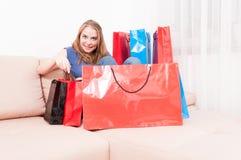 Damsammanträde på soffan som finner saker i shoppingpåsar Royaltyfri Fotografi