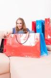 Damsammanträde på soffan som finner saker i shoppingpåsar Arkivfoton
