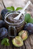 Damson jam. In a preserving glass on wooden ground Stock Image