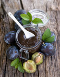 Damson jam. In a preserving glass on wooden ground Stock Photos