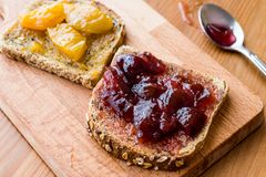 Damson Plum Jam on bread with Apricot jam. Royalty Free Stock Images