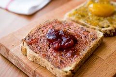 Damson Plum Jam on bread with Apricot jam. Stock Photos