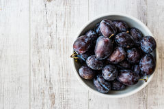 Damson Plum on white wooden surface. Organic food concept Royalty Free Stock Photos