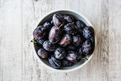 Damson Plum on white wooden surface. Organic food concept Royalty Free Stock Photo