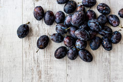Damson Plum on white wooden surface. Organic food concept Royalty Free Stock Images