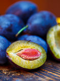 Damson plums. Halved plum and other whole plums on the table Stock Photography