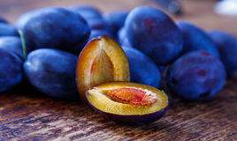 Damson plums. Halved plum and other whole plums on the table Stock Photos