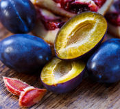 Damson plums and cake. Fresh damson plums with plum cake on the background Stock Images