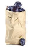 Damson plums. In a paper bag isolated on white background Royalty Free Stock Image