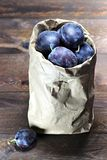 Damson plums. In a paper bag on wooden background Stock Photography