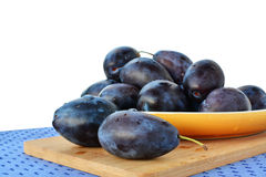 Damson plums on yellow plate over white Royalty Free Stock Photography