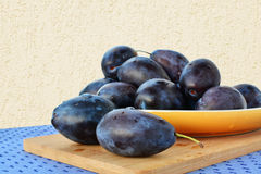 Damson plums on yellow plate Royalty Free Stock Images